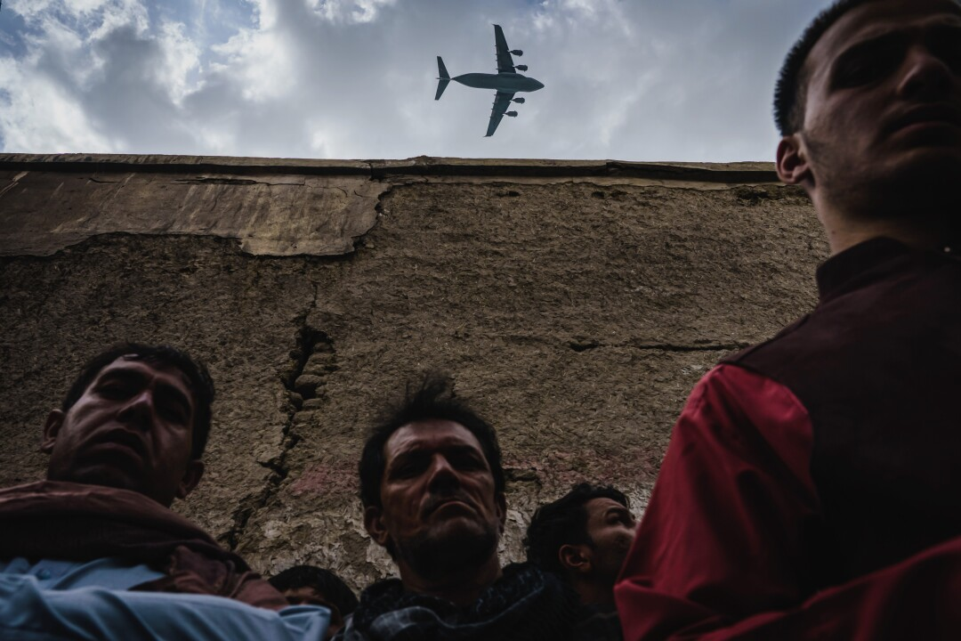 Gathering of people with military transport plane flying overhead