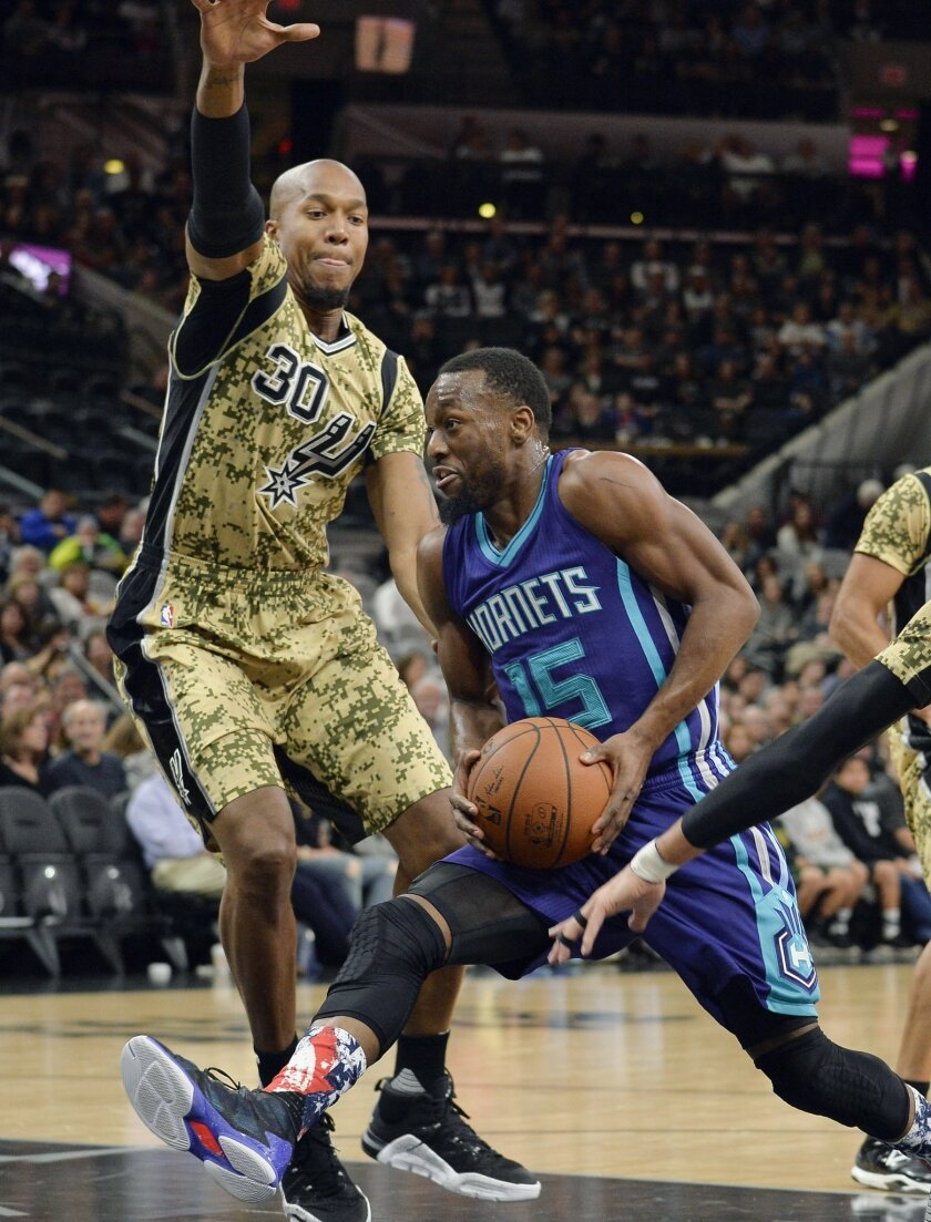 Charlotte Hornets guard Kemba Walker (15) is defended by San Antonio Spurs forward David West during the first half of an NBA basketball game, Saturday, Nov. 7, 2015, in San Antonio. (AP Photo/Darren Abate)