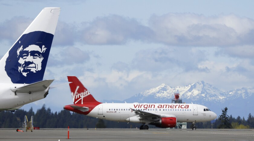 A Virgin America plane taxis past an Alaska Airlines plane waiting at a gate, Monday, April 4, 2016,