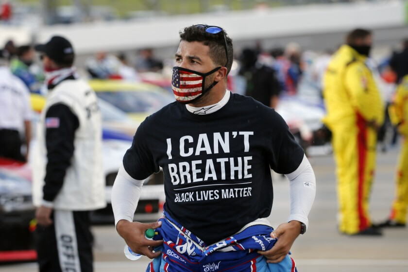 """FILE - In this June 10, 2020, file photo, driver Bubba Wallace, wearing an """"I Can't Breathe"""" T-shirt waits for the start of a NASCAR Cup Series auto race in Martinsville, Va. A predominantly white sport with deep Southern roots and a longtime embrace of Confederate symbols, NASCAR was forced last summer to face its own checkered racial history during the country's social unrest. (AP Photo/Steve Helber, File)"""