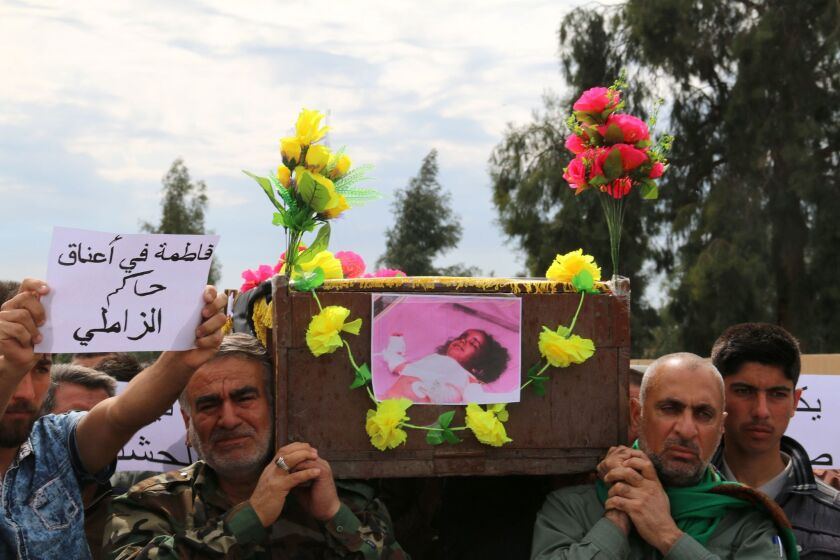Iraqi Sameer Wais, right, carries the coffin of his daughter Fatima, 3, who was killed in an ISIS chemical attack on the town of Taza.
