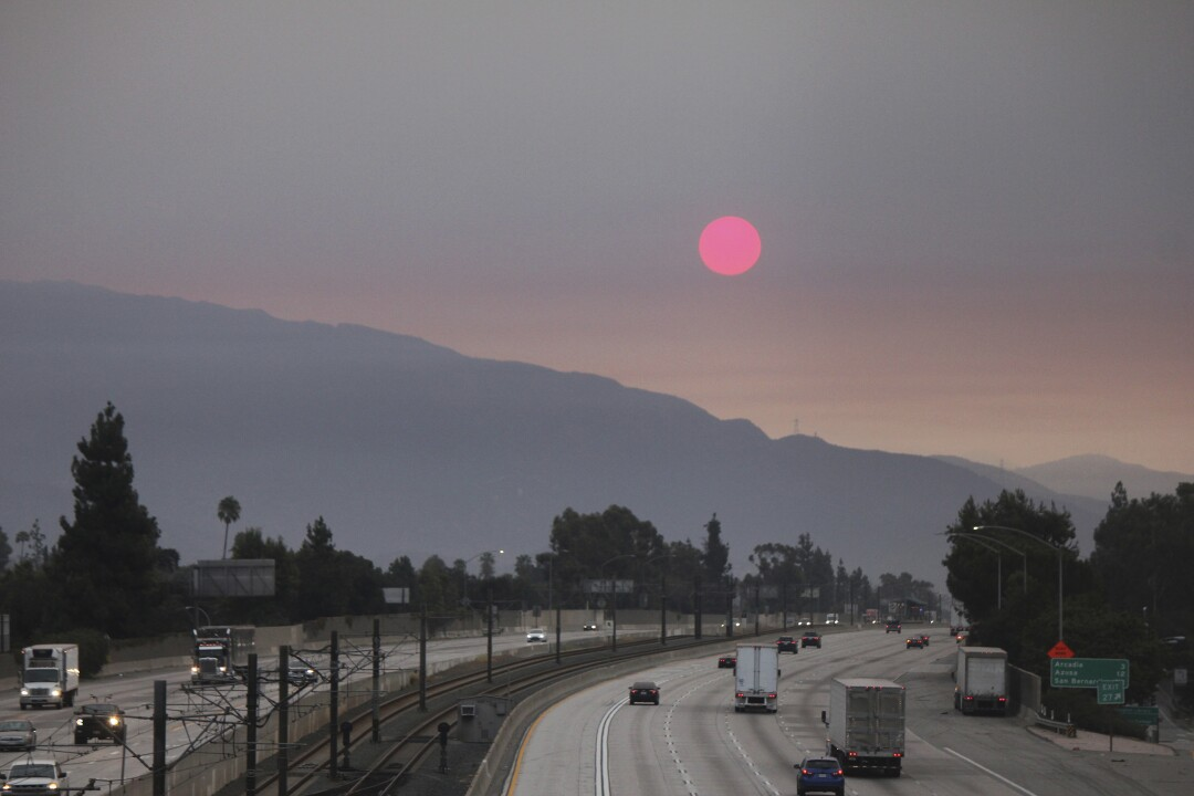 Smoke from wildfires burning east of Los Angeles dims the sunrise