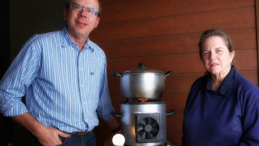 At Hi-Z technology, Fred Leavitt, vice president and Jill Elsner, CEO, stand next to a prototype stove that houses a thermoelectric module designed to allow the stove to generate up to 10 watts of usable power.