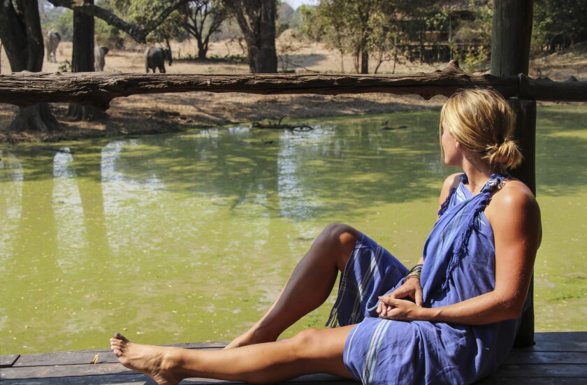 Writer Kathryn Romeyn admires elephants and impala across the watering hole at Bilimungwe Bush Camp in South Luangwa, Zambia. She wears a traditional African kikoi which, when wet, helps one cool off in the midday heat. (Bilimungwe has no electricity, air conditioning or fans.)