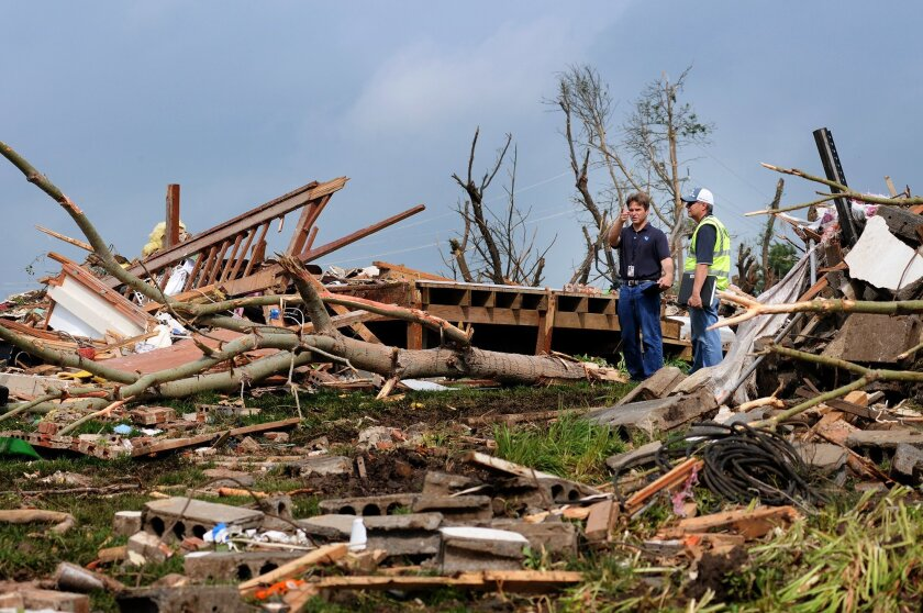 Meteorologists with the National Weather Service inspect the destruction Thursday morning, May 25, 2016, of a rural home north of Abilene, Kan. The home was destroyed Wednesday night by a tornado the stayed on the ground for 90 minutes and 25 miles. (Tom Dorsey/Salina Journal via AP)