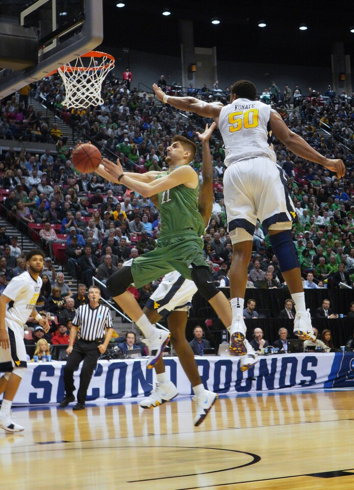 Marshall #11 Ajdin Penava is over powered under the basket by West Virginia #50 Sagaba Konate in the first half at the NCAA Division 1 Men's Basketball Championship at Viejas Arena at SDSU.