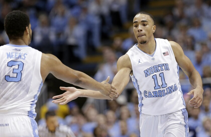 North Carolina's Brice Johnson (11) slaps hands with Kennedy Meeks (3) following Johnson's basket against Pittsburgh during the second half of an NCAA college basketball game in Chapel Hill, N.C., Sunday, Feb. 14, 2016. North Carolina won 85-64. (AP Photo/Gerry Broome)