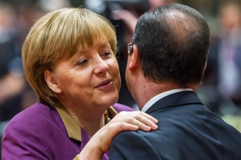 German Chancellor Angela Merkel, left, greets French President Francois Hollande during a round table meeting at an EU summit in Brussels on Friday, March 15, 2013. On the second anniversary of an uprising that evolved into Syria's brutal civil war, the European Union's national leaders will likely