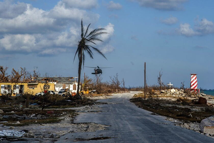 A helicopter flies over the village of High Rock after delivering emergency supplies in the aftermath of Hurricane Dorian in the Bahamas.