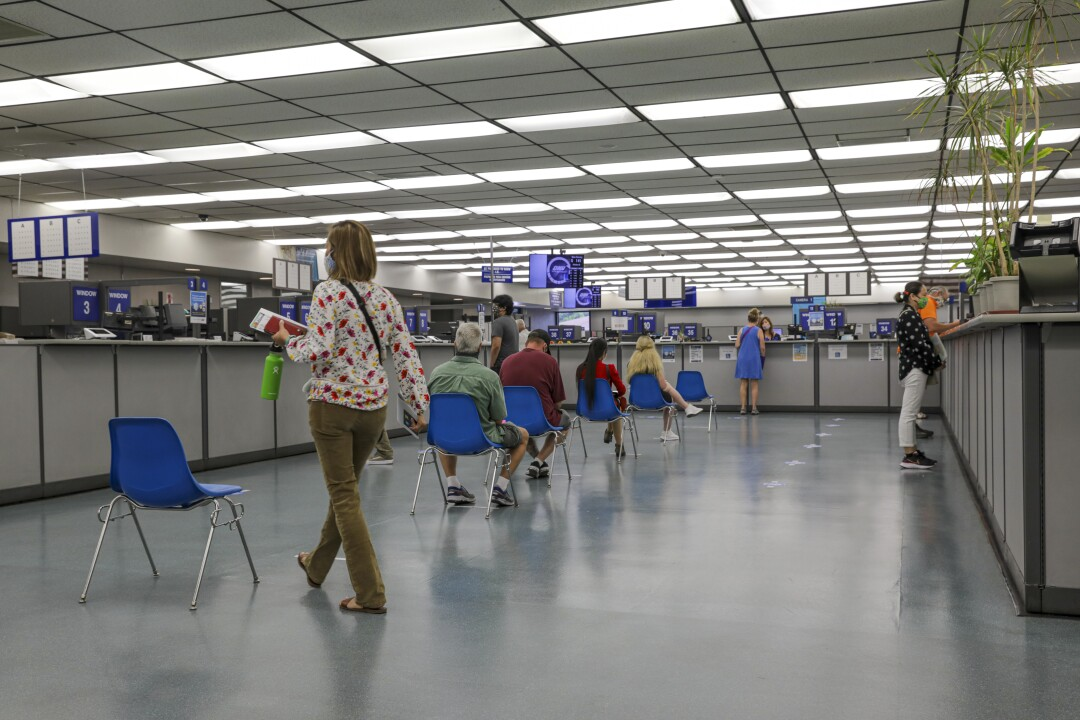 Customers sit in blue chairs spaced six feet apart in a line inside a DMV field office