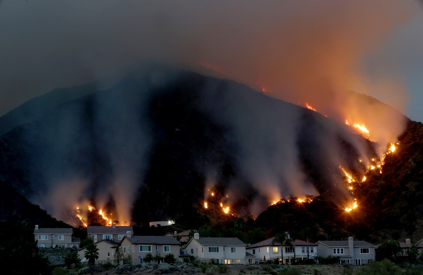 The Ranch fire burns in the hills above a cluster of homes along the San Gabriel River.