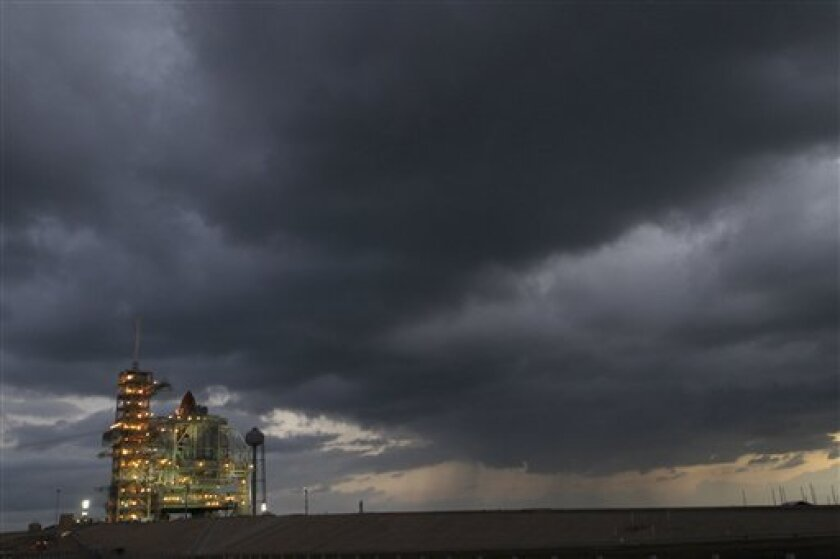 Storm clouds are seen at launch pad 39A over space Shuttle Discovery at the Kennedy Space Center in Cape Canaveral, Fla., Tuesday, Nov. 2, 2010. Discovery is scheduled to launch on Wednesday and weather predictions for launch are favorable. (AP Photo/John Raoux)