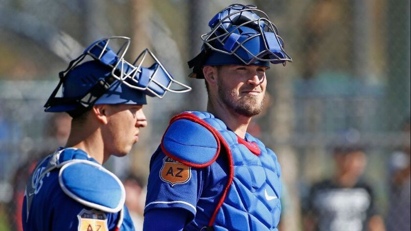 Dodgers catchers Yasmani Grandal and Austin Barnes pause at home plate during fielding drills at spring training on Feb. 21.