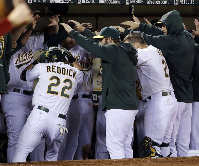 Oakland Athletics' Josh Reddick (22) celebrates his solo home run with teammates in the dugout during the sixth inning of a baseball game against the Los Angeles Angels Tuesday, April 28, 2015, in Oakland, Calif. (AP Photo/Marcio Jose Sanchez)