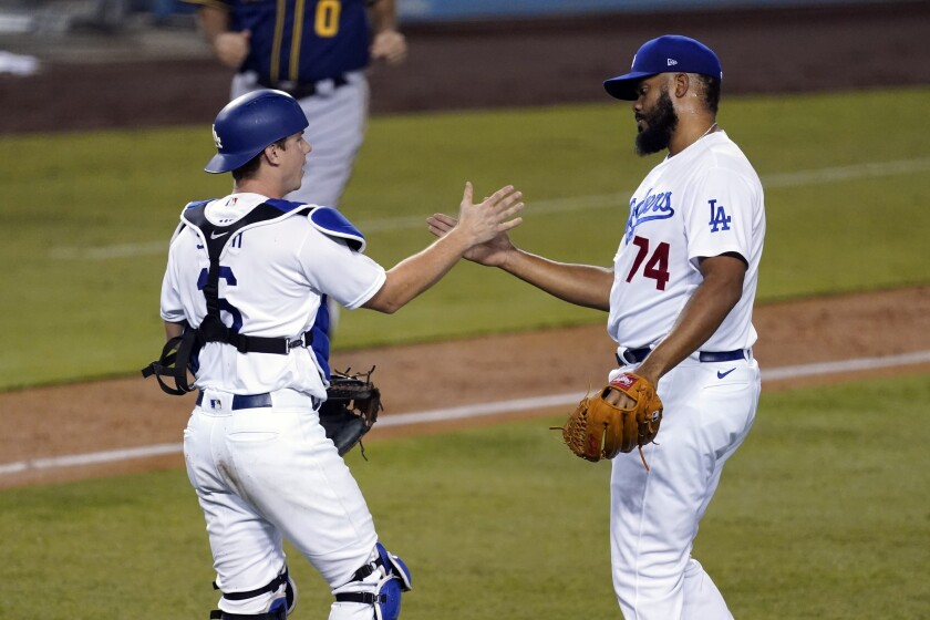 Dodgers relief pitcher Kenley Jansen, right, and catcher Will Smith celebrate a 4-2 win over the Milwaukee Brewers.