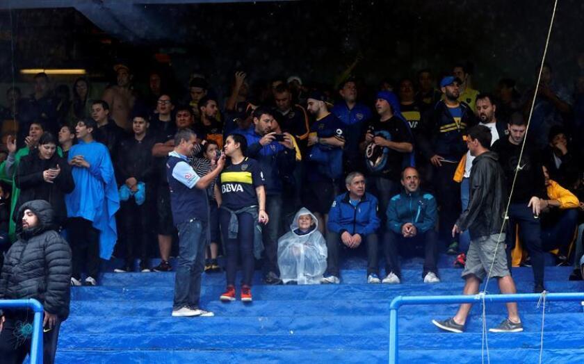 Boca Juniors fans take shelter from the rain at the La Bombonera stadium, in Buenos Aires, Argentina, Nov. 10, 2018. EPA-EFE/Juan Ignacio Roncoroni