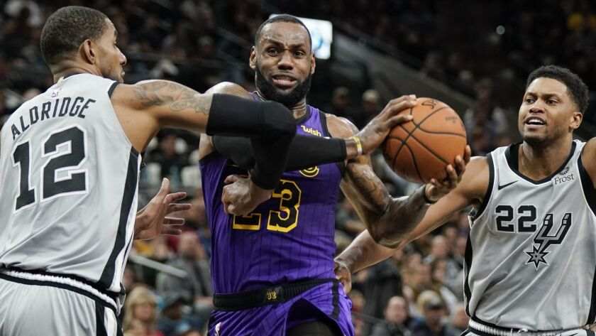 Lakers forward LeBron James drives to the basket between Spurs forwards LaMarcus Aldridge and Rudy Gay (22) during the first half Friday night.