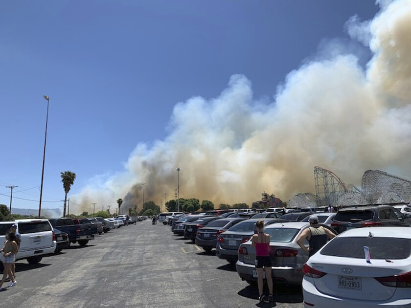 Heavy smoke from a fast-moving brush fire surrounds Six Flags Magic Mountain.