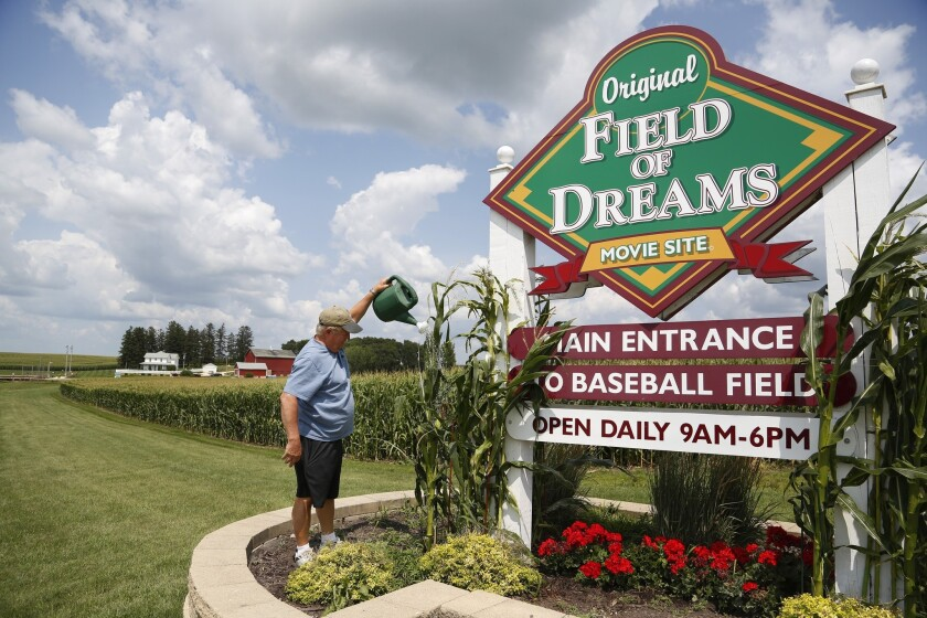 Former field co-owner Don Lansing waters the landscaping around the sign marking the entrance of the site in Dyersville, Iowa.