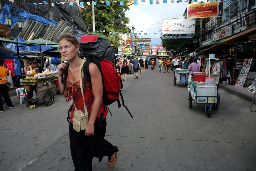 A backpacker walks down Khaosan Road, a favorite tourist destination.
