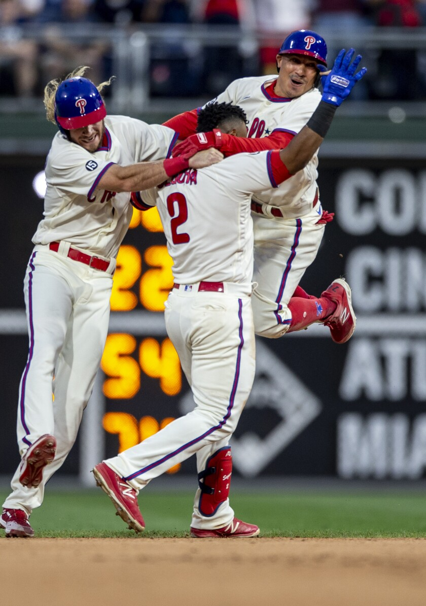 Philadelphia Phillies' Travis Jankowski, left, Jean Segura (2) and Ronald Torreyes, right, celebrate after the Phillieos defeated the New York Yankees 8-7 in 10 innings in a baseball game Saturday, June 12, 2021, in Philadelphia. (AP Photo/Laurence Kesterson)