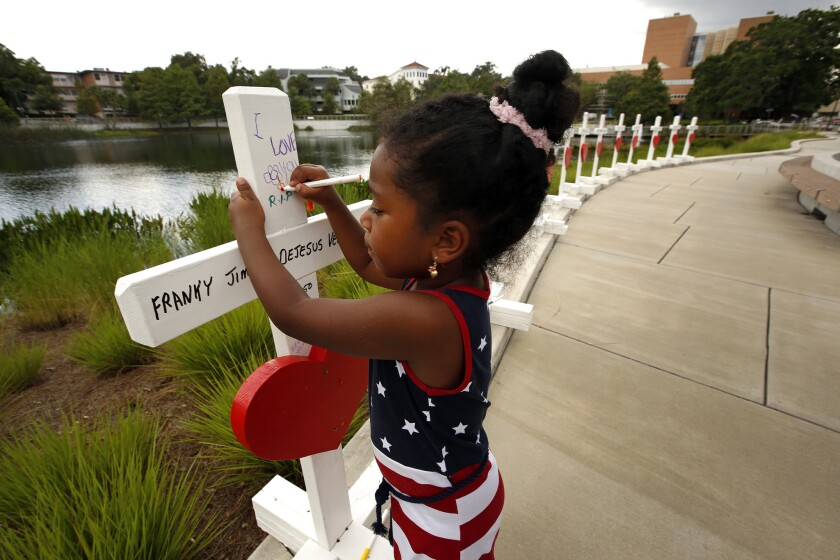 Inaya Bava, 5, on June 16, 2016, draws on crosses set up to remember the victims of the Pulse nightclub shooting at the Orlando Regional Medical Center.