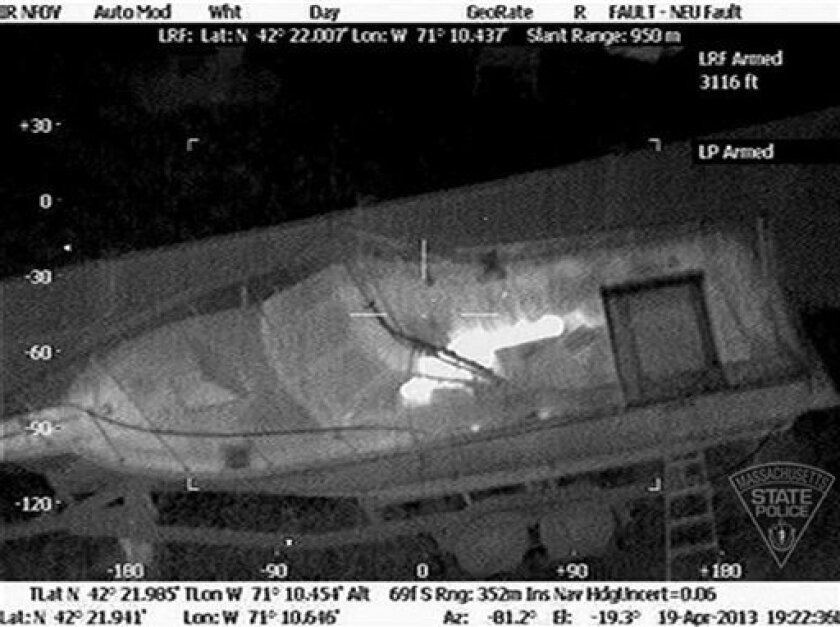 This Friday, April 19, 2013 image made available by the Massachusetts State Police shows 19-year-old Boston Marathon bombing suspect, Dzhokhar Tsarnaev, hiding inside a boat during a search for him in Watertown, Mass. He was pulled, wounded and bloody, from the boat parked in the backyard of a home in the Greater Boston area. Two U.S. officials say the surviving suspect in the Boston bombings was unarmed when police captured him hiding inside a boat in a neighborhood back yard. Authorities origi