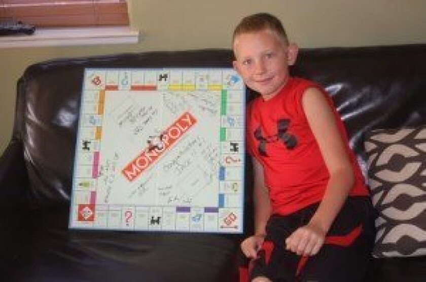 Jack Munson with the Monopoly board on which he played when he won a Monopoly tournament. It was signed by all his competitors. Ashley Mackin
