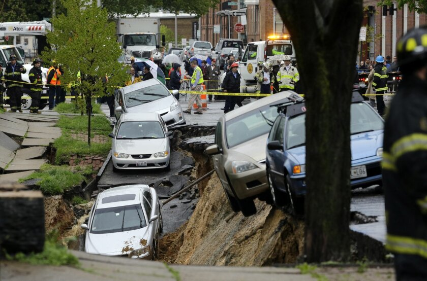 Cars sit on the edge of a sinkhole in the Charles Village neighborhood of Baltimore, Wednesday, April 30, 2014, as heavy rain moves through the region. Road closures have been reported due to flooding, downed trees and electrical lines elsewhere in the Mid-Atlantic. The National Weather Service iss