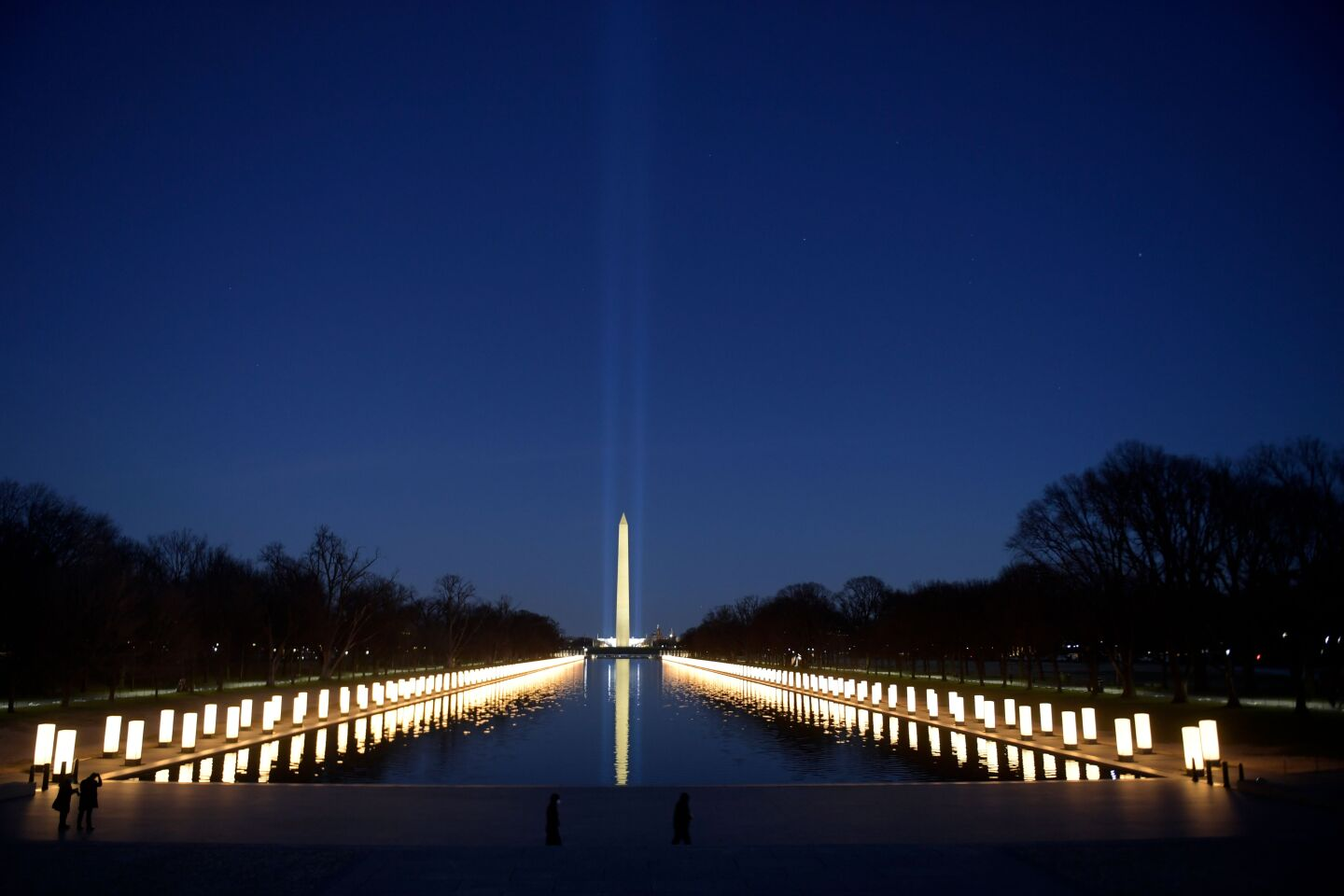 The Reflecting Pool is lighted as a Covid-19 Memorial in front of the Washington Monument in Washington, DC, on January 19, 2021 during a vigil to honor the lives of those lost to Covid-19. (Photo by Patrick T. FALLON / AFP) (Photo by PATRICK T. FALLON/AFP via Getty Images)