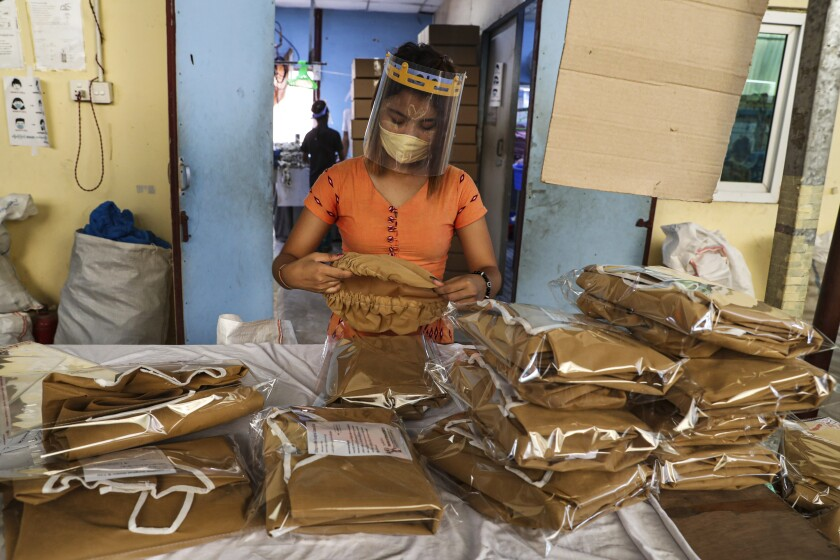 FILE - In this May 28, 2020, file photo, a woman wearing face mask and face shield to help curb the spread of the new coronavirus checks surgical gown at a packing session of a garment factory at Industrial Zone in Yangon, Myanmar. The coronavirus pandemic has slammed the apparel industry, leaving many of the 65 million Asian garment factory workers struggling as factories close or cut back on wages, and the International Labor Organization is urging the industry to do more to protect them. (AP Photo/Thein Zaw, File)