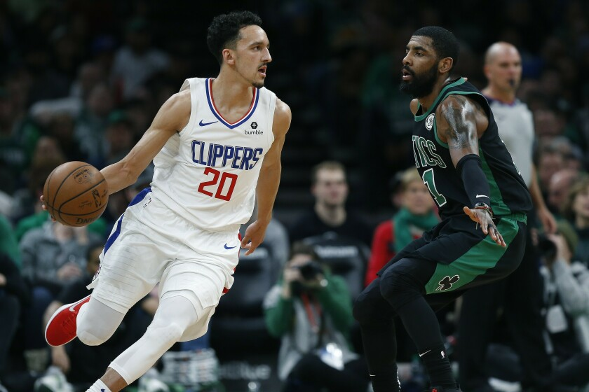 Landry Shamet drives past Boston Celtics guard Kyrie Irving during his debut for the Clippers at TD Garden on Feb. 9, 2019.