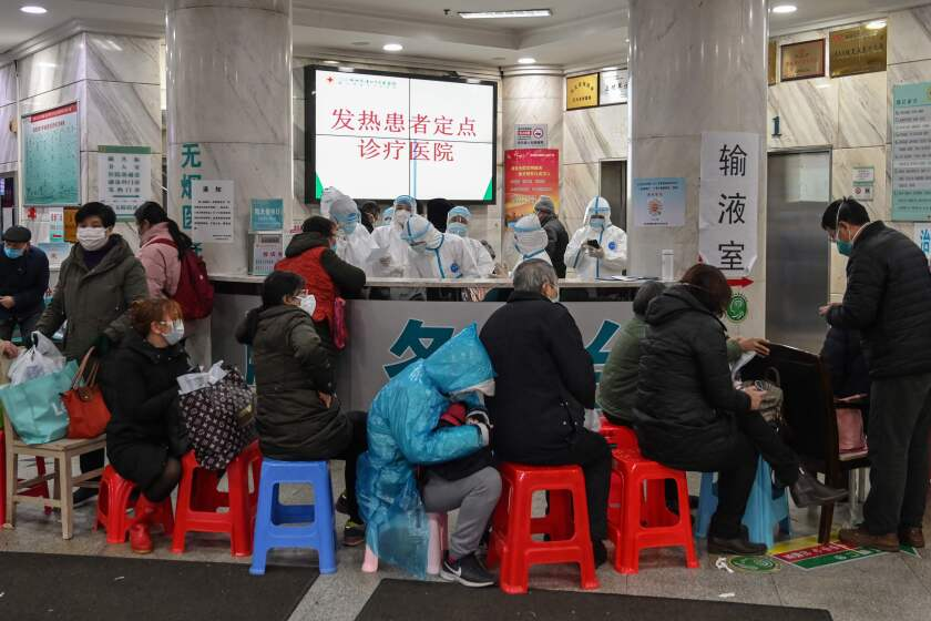 People wait to be seen by medical staff at Wuhan Red Cross Hospital in Wuhan.