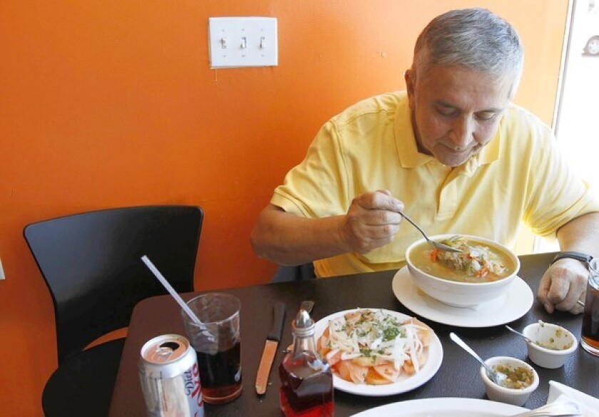 Francisco Aldoney customizes his bowl of cazuela de vacuno (a traditional Chilean beaf stew) at Chilenazo in Canoga Park.