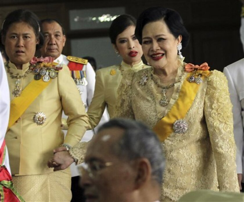 FILE - In this Dec. 5, 2011 file photo, Thailand's Queen Sirikit, right, accompanies King Bhumibol Adulyadej, foreground, as the king leaves Siriraj hospital to the Grand Palace for a ceremony celebrating his birthday in Bangkok, Thailand. Doctors have advised Thailand's Queen Sirikit to rest after an exam showed a slight reduction in blood flow to her brain. The Royal Palace announced Sunday, July 22, 2012, that the 79-year-old queen had felt dizziness and staggered slightly while walking for exercise a day earlier. However, she remained conscious and could speak. Crown Princess Sirifhorn is at left. (AP Photo/Apichart Weerawong, File)