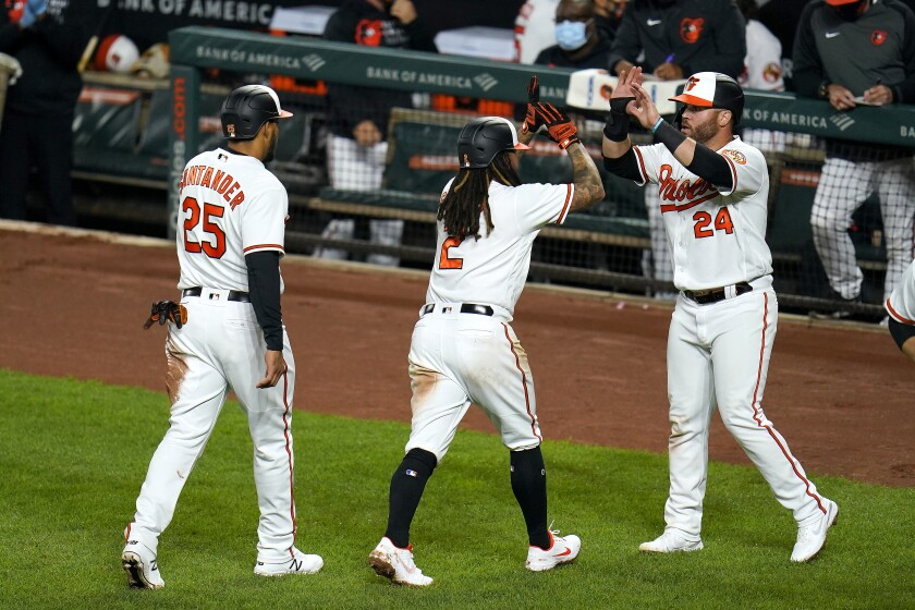 Baltimore Orioles' Anthony Santander (25), Freddy Galvis (2) and DJ Stewart (24) react after they scored on a bases loaded double by Maikel Franco, not visible, during the third inning of the second game of a baseball doubleheader against the Seattle Mariners, Tuesday, April 13, 2021, in Baltimore. (AP Photo/Julio Cortez)