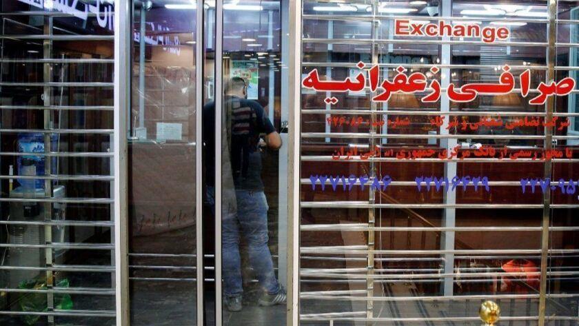 An Iranian man stands inside a money exchange shop in Tehran.