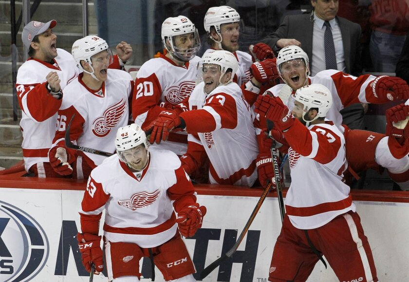 Detroit Red Wings players celebrate with center Darren Helm, front left, after his game-winning shootout goal in an NHL hockey game against the Minnesota Wild in St. Paul, Minn., Saturday, April 4, 2015. The Red Wings won 3-2. (AP Photo/Ann Heisenfelt)