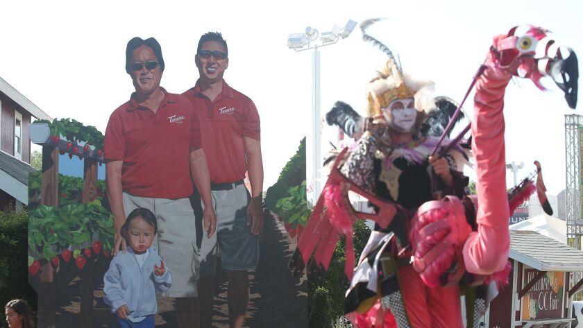 The faces of Glenn Tanaka and his son, Kenny, of Tanaka Farms, greets fair-goers at the main entranc