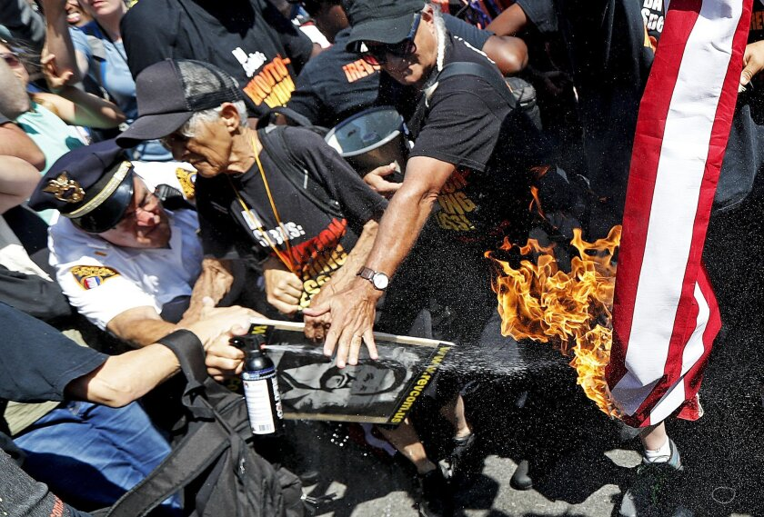 A law enforcement officer tries extinguish a burning American flag, Wednesday, July 20, 2016, in Cleveland, during the third day of the Republican convention.  (AP Photo/John Minchillo)