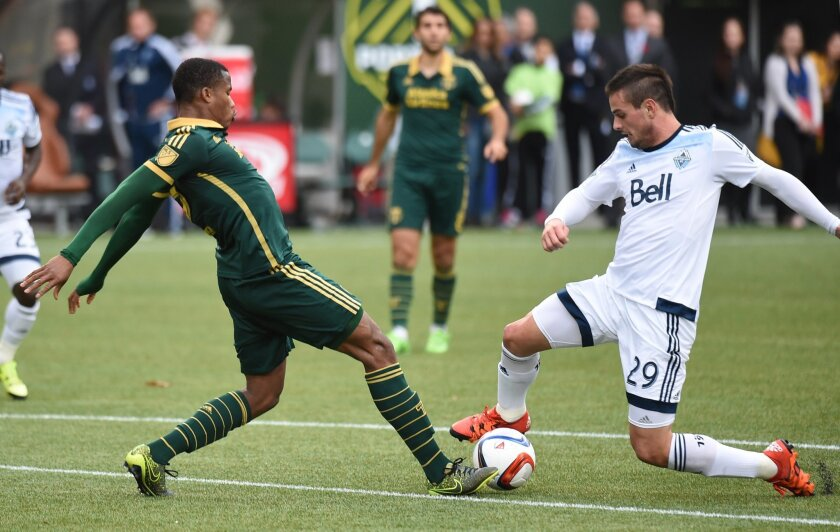 Portland Timbers defender Alvas Powell (2) goes after a ball with Vancouver Whitecaps forward Octavio Rivero (29) during the first half of an MLS western conference semifinal soccer match in Portland, Ore., Sunday, Nov. 1, 2015. (AP Photo/Steve Dykes)