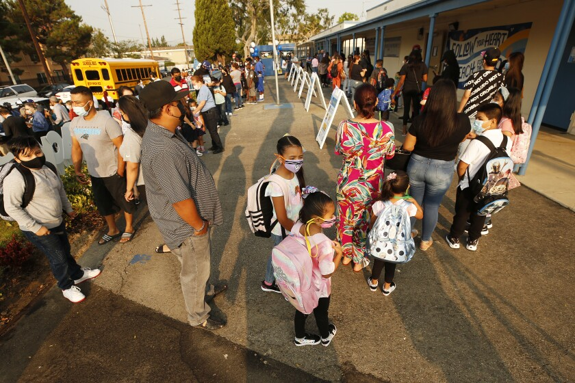 Students and parents wait in line to enter Normont Elementary School to celebrate the first day of in class instruction