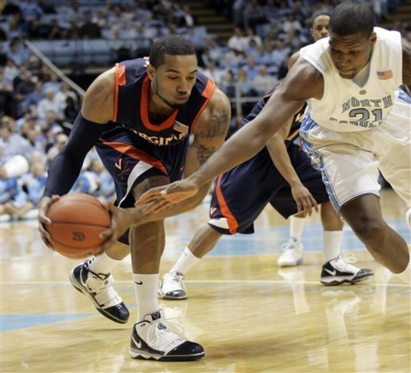 Virginia forward Mike Scott keeps the ball from North Carolina forward Deon Thompson (21) during the first half of an NCAA college basketball game in Chapel Hill, N.C., Sunday, Jan. 31, 2010. (AP Photo/Jim R. Bounds)