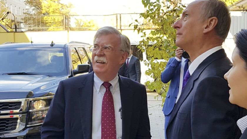 U.S. national security advisor John Bolton, left, and Russian Security Council Chairman Nikolai Patrushev chat before their official talks in Moscow on Monday.