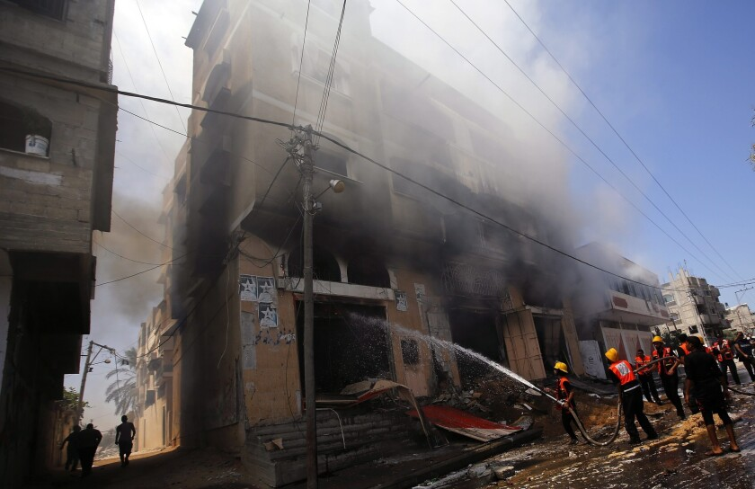 Palestinian firefighters douse a blaze in a house after Israeli airstrikes in Gaza City on Aug. 23.