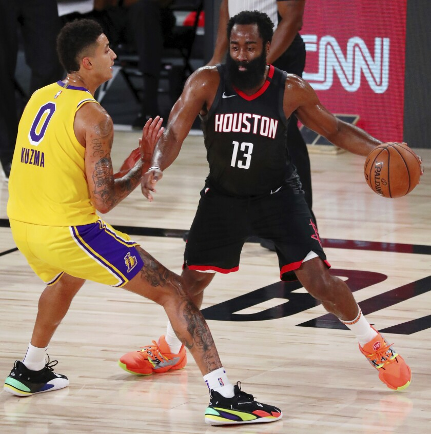 El jugador de los Rockets de Houston James Harden (13) dribla ante la defensa de su rival de los Lakers, Kyle Kuzma.