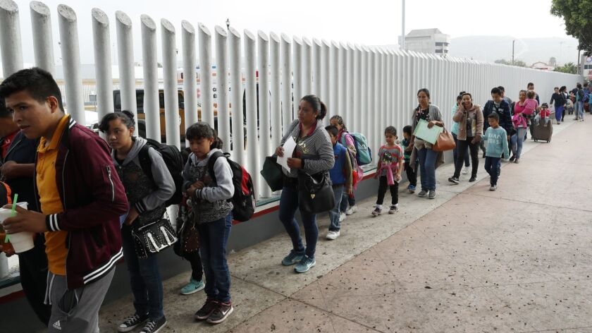 People line up to cross into the United States to begin the process of applying for asylum Thursday,