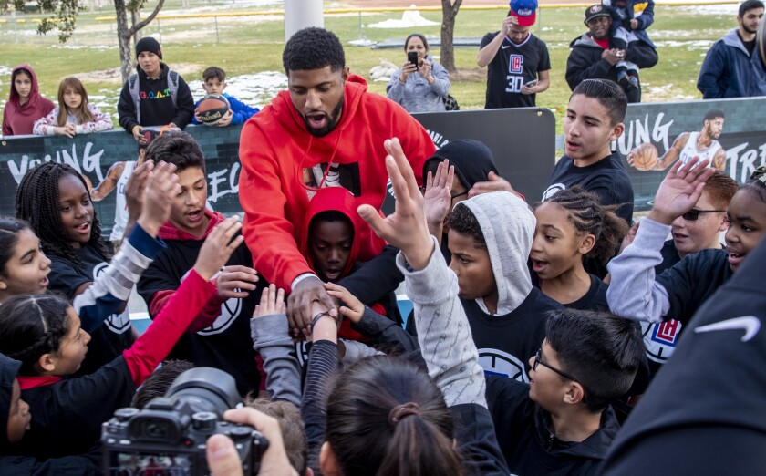 Clippers star Paul George greets young fans after posing for photos on refurbished courts at Domenic Massari Park, where he grew up playing basketball in Palmdale.