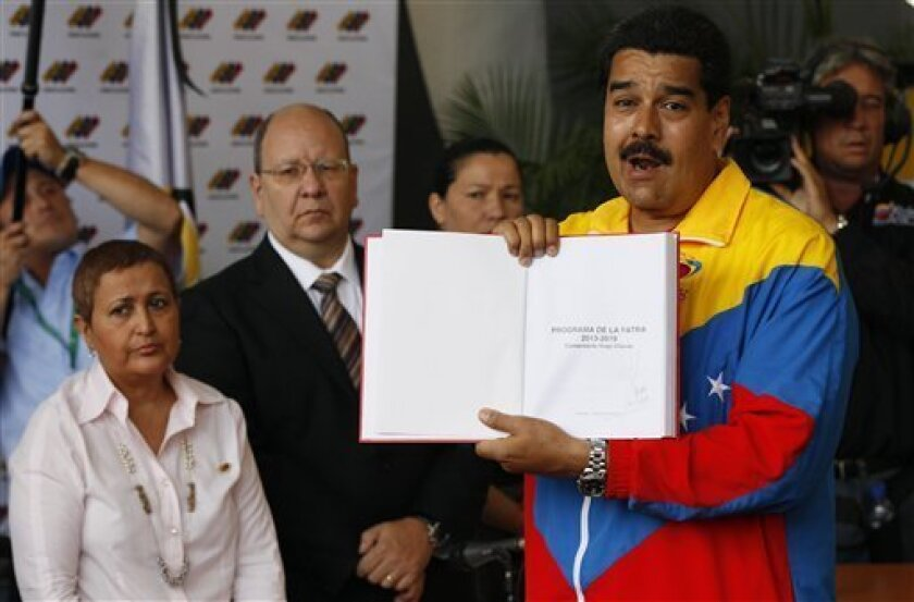 "ADDS REFERENCE TO CHAVEZ'S SIGNATURE - Venezuela's acting President Nicolas Maduro holds up what he says was the government plan created by late President Hugo Chavez, titled ""Homeland Program 2013-2019. Commander Hugo Chavez,"" with Chavez's signature, after registering his candidacy for president to replace late President Hugo Chavez in Caracas, Venezuela, Monday, March 11, 2013. Behind left stands Tibisay Lucena, president of the national electoral council. Presidential elections were announce"
