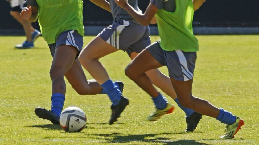 LOS ANGELES, CA. - NOVEMBER 5, 2014: Sam Mewis (CQ), center, dribbles the ball during a scrimmage d